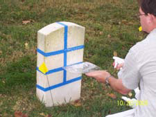Figure 5. Jason Church applies WEG Marble Cleaner to a taped test patch. He holds a piece of acetate to the stone surface to prevent runoff below the patch. All cleaners were applied following manufacturerís recommendations for dwell time, etc. The stones were subsequently rinsed with water, again using the acetate to prevent runoff.