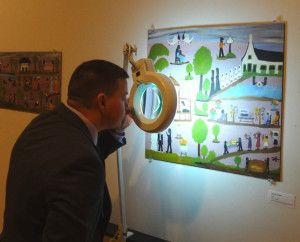 A participant inspects a forgery imitating folk artist Clementine Hunter's work during Divine Disorder, Conserving the Chaos held in Natchitoches, LA.