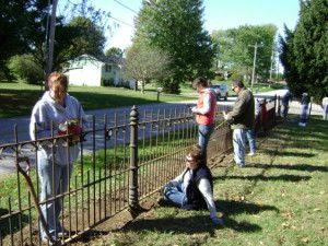 Students clean an historic fence during the Preservation of Ornamental Iron Workshop held in Bloomington, IN.