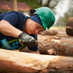A member of the HOPE Crew shaves down a timber.