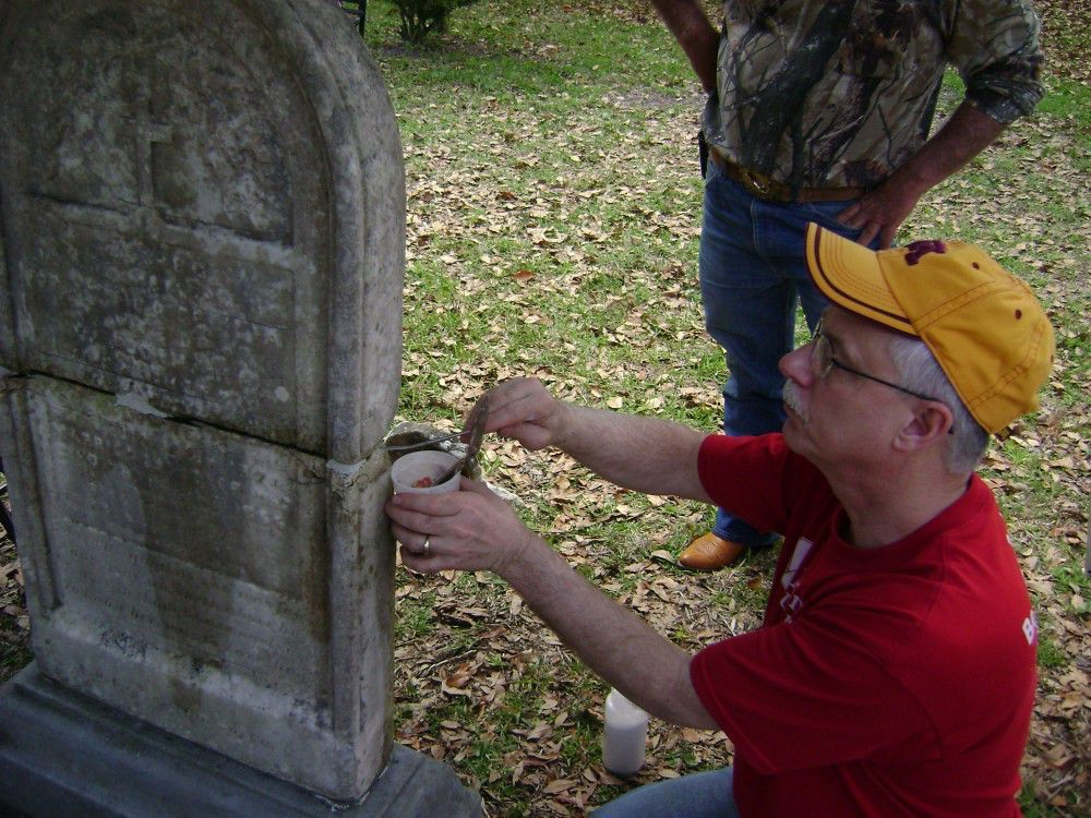 A participant repairs a grave marker with during a workshop held in St. Augustine, FL.