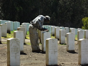 This image show the inappropriate use of a wire brush on a power drill to alter the surface of a grave marker.