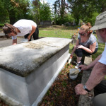 Summer interns Sarah Hunter and Stephanie Byrd assist Bob Adams in applying limewash.