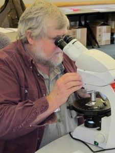 Michael Trinkley carefully examines a thin section under the microscope.