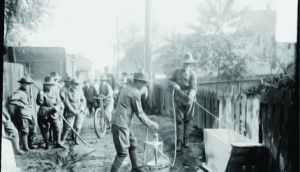 Boy Scouts clean up alleys on Clean Up Day in the Near South Side community area of Chicago circa 1915. Two scouts are whitewashing a wooden bin while others look on. (DN-0064648, Chicago Daily News negatives collection, Chicago Historical Society.)