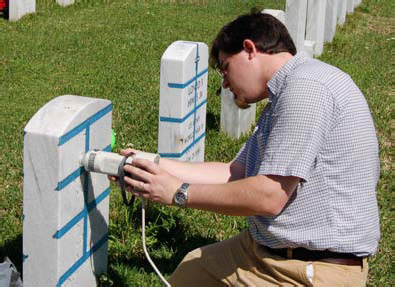 Jason Church positions the head of the Minolta colorimeter for measurements on a headstone in Alexandria National Cemetery.