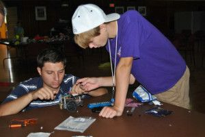 NCPTT intern Stan Ponomarev demonstrates robot construction to a student at the 2012 Robotics Camp.