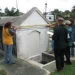 A group of workshop participants do a conditions assessment exercise on a small mausoleum. Photo: Mary Striegel.