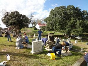 Workshop participants clean marble headstones in the Jewish Section of Natchez City Cemetery