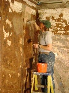 Applying limewash to the repaired walls.