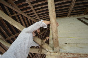 Ed Fitzgerald works with a partner to measure the length of the timber on the north wall.