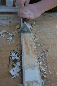 Scraping deteriorated paint from wooden sash after using infrared heat to soften the paint.