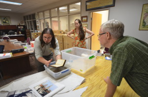 Jason Church talks with participants about drying water logged books.