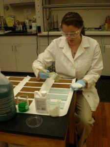Anna Muto is applying Rust Reformer rust converter to corroded metal samples.