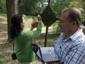 Carol Chin and Curtis Desselles use NCPTT's low cost eddy current analyzer to study an obscured inscription on an iron cross.