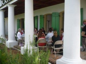 Participants and presenters discussing workshop on the porch at the Pitot House in New Orleans, LA.