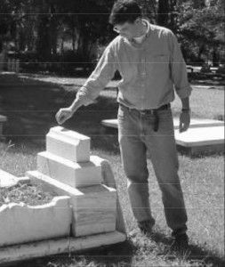 Andrew Ferrell examines a broken headstone of a tomb in American Cemetery, Natchitoches, Louisiana.