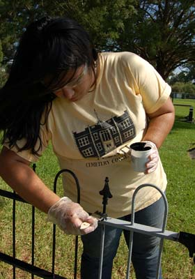 Conservator Bianca Garcia applies a finish coat during a fence restoration.