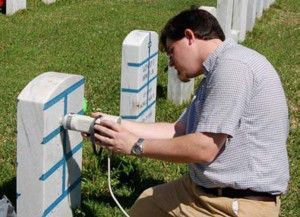 Jason Church positions the head of the Minolta colorimeter for measurements on a headstone in Alexandria National Cemetery.  Photo by Mary Striegel