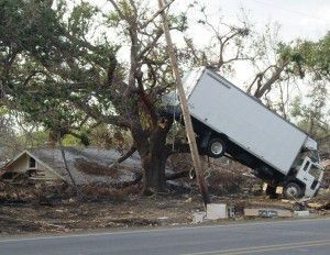 Panel truck stuck in a tree next to a destroyed home.